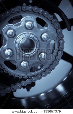 Color image of some motorcycle chains and sprockets.
