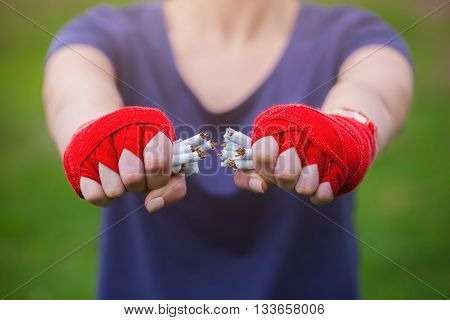 Hands girls rolled up in boxing bandages break a stack of cigarettes. Moitvatsiya to a healthy lifestyle. Sports against smoking. No smoking.
