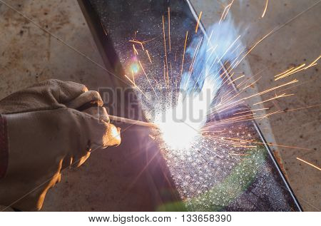 Shield metal arc welding joint steel in manufacturing work shop.