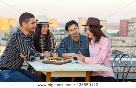 Young People Appointment at Outdoor Roof Top Cafe Table with Pizza and Drinks on Wood Desk and Evening Urban Background Multi-Ethnic Company
