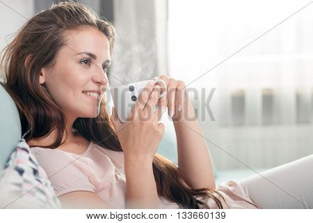 Young Woman Sitting On Couch At Home And Drinking Coffee. Casual Style Indoor Shoot