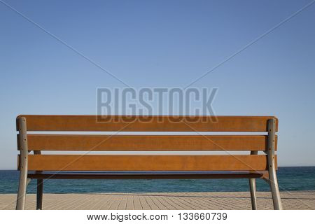 Bench made of wood at the ocean. Clear cloudless blue sky, the turquoise sea and parts of the pedestrian walk as background.
