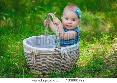 Little girl with a blue bow on her head sitting in wicker white basket sunny day in the park on the grass.