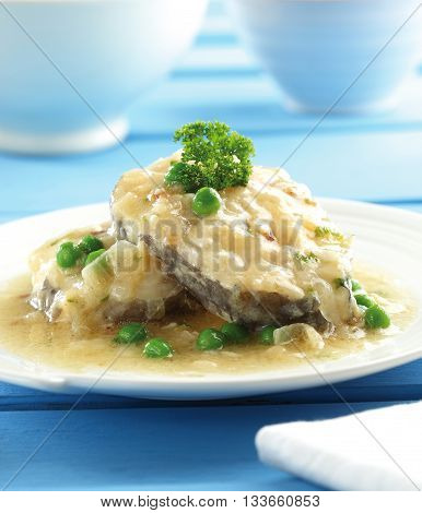 A plate of conger fish with onion sauce and green peas.
