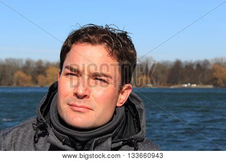Portrait of handsome young man looking critical in front of a lake.