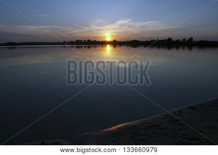 Sandy shore of the lake at sunset