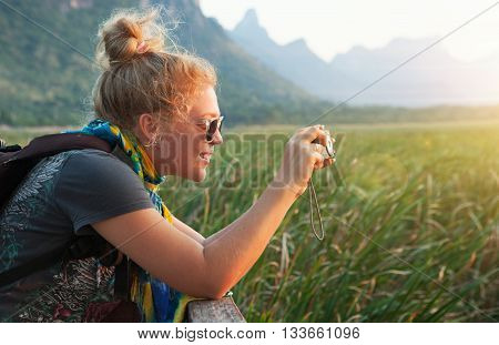portrait of young beautiful girl is shooting sunset in summer environment