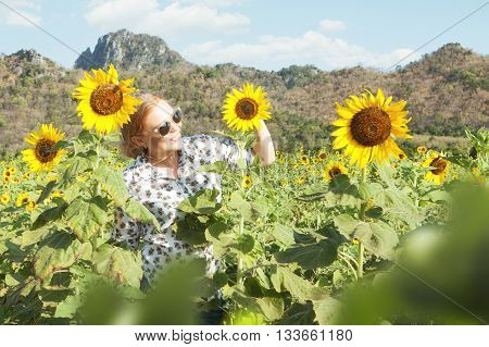 portrait of young smiling happy  woman getting through the sunflower field