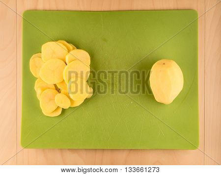 Whole and sliced peeled potatoe on used green plastic board, simple food preparation illustration, vegetarian dieting, top view still life with center composition