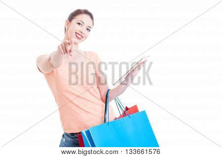 Woman Carrying Shopping Bags Pointing At Camera And Holding Tablet