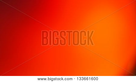 Unfocused blurred texture pattern abstract background with orange red tones in warm colors with gentle black parts in the corners