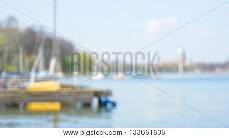 Overexposed blurred unfocused lake scene with yellow sailboat anchored at wooden jetty. Trees without leaves and blurry cityscape in the background.