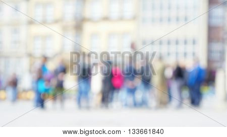 Blurred unfocused queue of unidentified people in front of overexposed row of old houses.