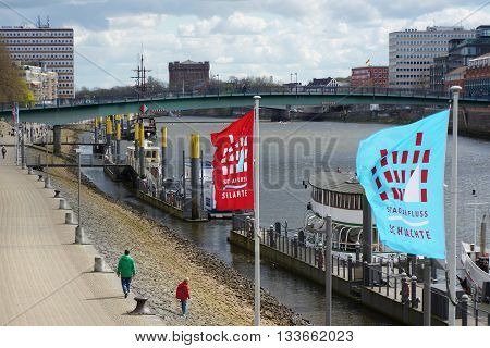 Bremen, Germany, 17th April 2016. River Weser in city center. Sightseeing boats anchored at river bank. Text on flags: 'Town at River - Schlachte'. (Schlachte is the name of the quarter).