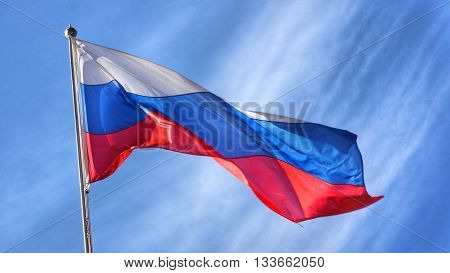 Flag of Russia. Russian Flag on flagpole waving unfavorable due to windy conditions in front of blue sky.