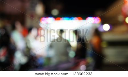 Blurred unfocused scene with people ordering food in front of an illuminated food booth. Red blue violet and white blurry lights.
