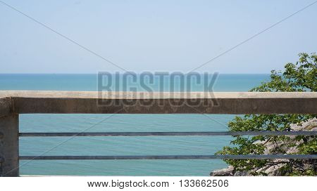 Balcony Railing made of Concrete and Metal above the Blue Ocean and in front of the Blue Cloudless Sky. Some Green Plants on the Right Side.