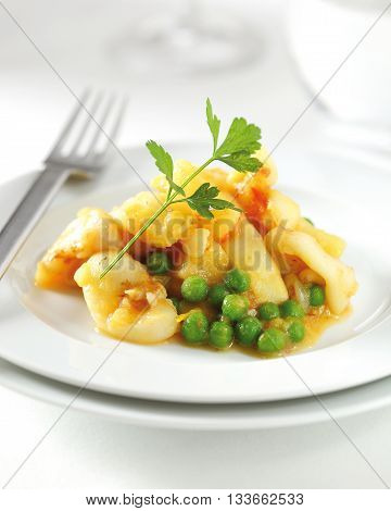 A squid appetizer with sauce and green peas.