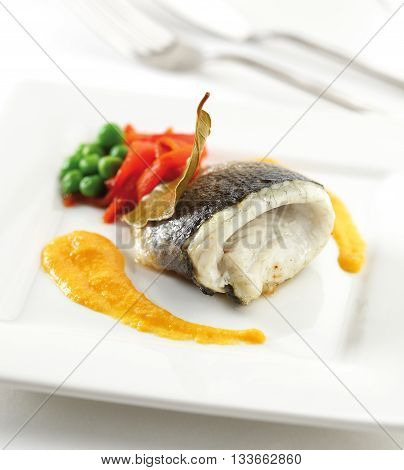 Sea bass fillet on a plate with sauce peppers and green peas.