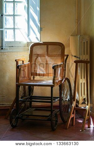 Old wooden wheelchair in the interior. Pale yellow walls window grille and radiator.