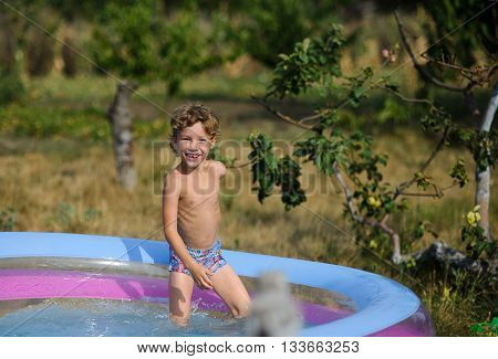 The boy in the inflatable pool. The child cheerfully looks in a camera. On the boy wet pants. On a background a garden.