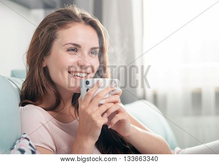 Smiling Woman Sitting On Couch At Home And Drinking Coffee. Casual Style Indoor Shoot