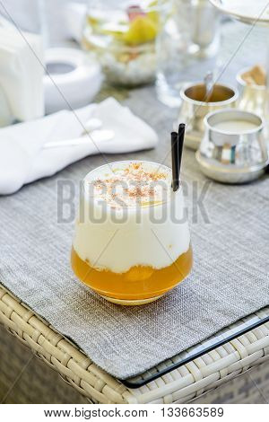 Yellow cocktail with thick white foam, and two cocktail tubules