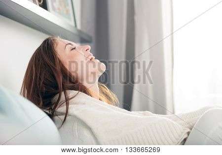 Happy Young Woman Lying On Couch At Home And Laughing. Casual Style Indoor Shoot