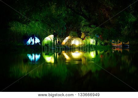 Illuminated tent on a lake with reflexions Danube Delta Romania