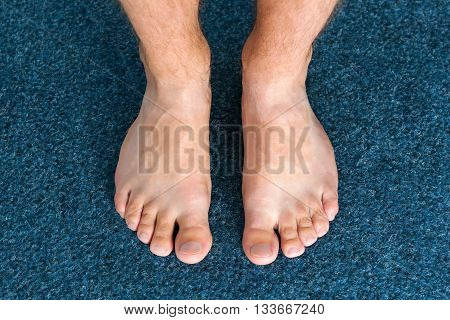 Male feet steps on blue background, hygiene