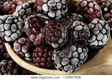 Macro of a wooden spoon filled with frozen blackberries with shallow depth of field.