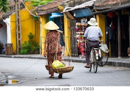 Unidentified old woman in traditional Vietnamese clothes carrying buskets with food on the street in Hoi An city. Hoian is recognized as a World Heritage Site by UNESCO