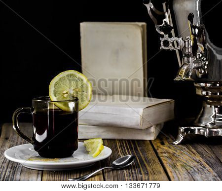 old samovar and tea Cup with lemon on a wooden background with books