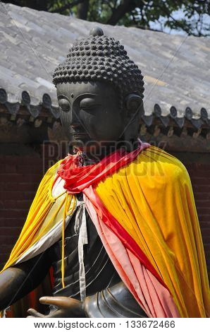 A metal Buddha statue wrapped in silk robes at the Shaolin Temple in Dengfeng city located in Henan province China.