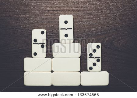 domino pieces forming podium win concept background