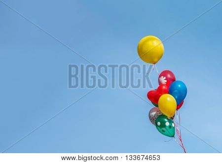 Colorful party balloon floating in mid air against a bright blue sky.