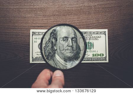 authentication of one hundred dollars banknote on wooden background