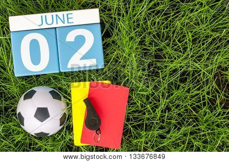 June 2nd. Image of june 2 wooden color calendar on green grass background with football outfit. Summer day.