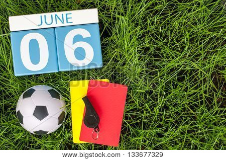 June 6th. Image of june 6 wooden color calendar on green grass background with football outfit. Summer day.