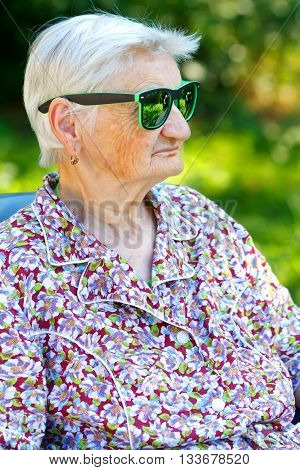 Photo of a senior woman wearing trendy sunglasses