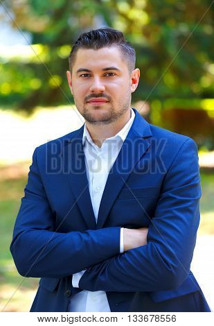 A successful businessman standing in the park