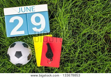 June 29th. Image of june 29 wooden color calendar on green grass background with football outfit. Summer day.