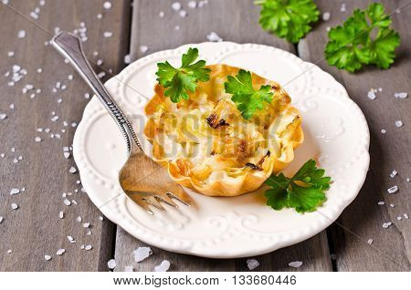 Homemade tartlets with cabbage on a wooden background. Selective focus.