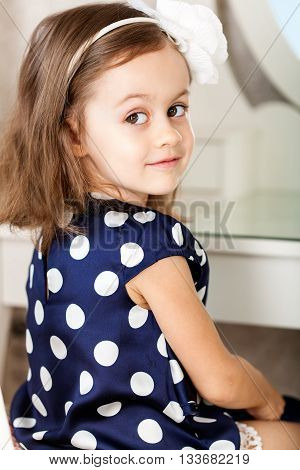 Little girl in blue dress is hairbrushing