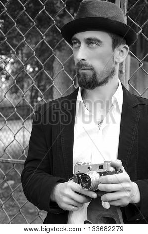 Retro style photographer with old camera. Young hotographer. Photographer holding retro vintage camera. Black and white photography