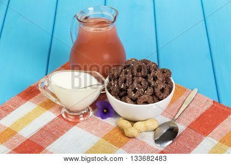 A jug of juice, yogurt, a bowl of corn rings with cocoa and sesame seeds, peanuts, spoon on a wood background painted in blue.