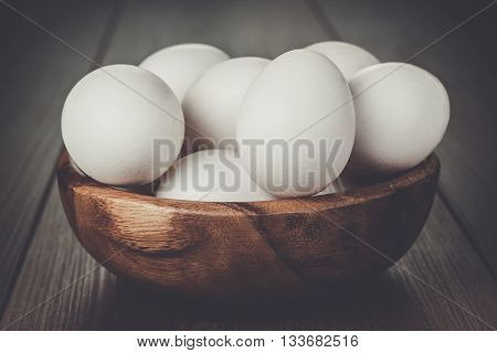 some eggs in wooden bowl on the table