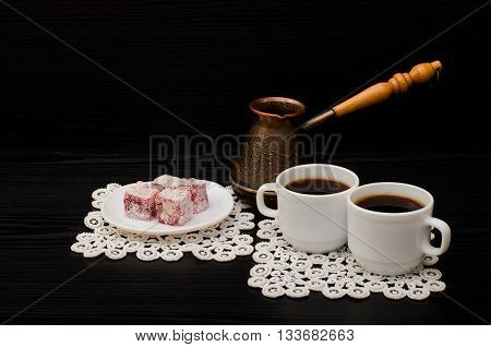 Two mugs of coffee Turkish delight and cherry pots on a black background