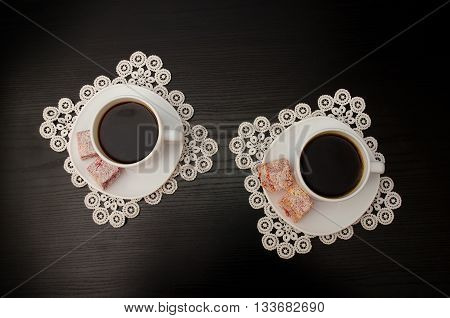 Top view of two mugs of coffee on a saucer with Turkish Delight. Lacy napkins black table