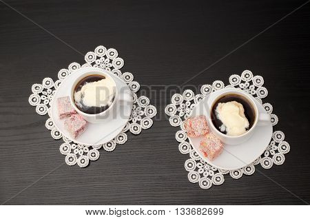 Top view of two mugs of coffee with ice cream on a saucer with Turkish Delight. Lacy napkins black table